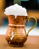 Turkish Drink Ayran or Buttermilk with foam in copper cup. Royalty Free Stock Photo