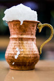 Turkish Drink Ayran or Buttermilk with foam in copper cup. Royalty Free Stock Photography