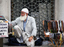 Turkish elderly man with a white beard sells muslim prayer beads tasbih on the street near the entrance to the mosque Stock Photo