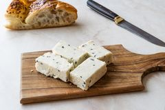 Turkish Feta Cheese with Black Cumin Sesame Seeds on Wooden Surface with Knife.
