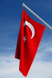 Turkish Flag. On a flagpole against the blue sky stock illustration