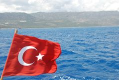 Turkish flag on blue mediterranean sea shape. Turkey, wind, background, sky, red, national, wave, beach, hotel, kemer, white, boat, patriotism, star, color stock photo