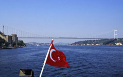 Turkish flag on Bosphorus. The red turkish flag of a boat is floating in the wind in the middle of Bosphorus. On left is the European shore, on right the Asian royalty free stock photography