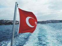 Turkish flag on ferry. Red Turkish flag on ferry boat with city on background Stock Images