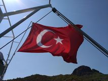 Turkish Flag. A flag in the wind develops against the blue sky. Stock Photo