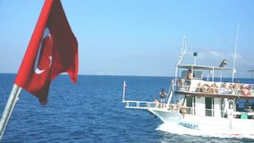 Turkish flag floats in mid air at the back of a boat. While other passenger boat cruises in distance in Datca, Turkey stock video footage