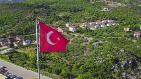 Turkish flag flying on background of mountains. Clip. Top view of beautiful flag flying on faith on background of green. Mountains. Summer mountain landscape stock footage