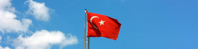 Turkish flag flying in the wind, with blue sky Royalty Free Stock Photos