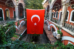Turkish flag hanging in courtyard. A red Turkish flag hangs in a lush courtyard in the afternoon Stock Photos