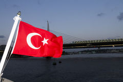 A turkish flag with a large Istanbul bridge in the background Stock Photo