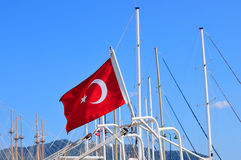 Turkish flag on the mast of a yacht on a background of blue sky Stock Image