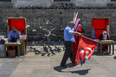 A Turkish flag seller walks past the 400 year old New Mosque in Eminonu in Istanbul in Turkey. Stock Image