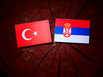 Turkish flag with Serbian flag on a tree stump isolated. Turkish flag with Serbian flag on a tree stump royalty free stock photography