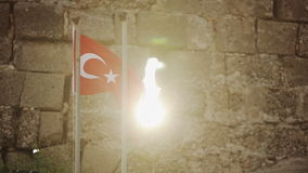 Turkish flag on a stone wall background at sunset stock video footage