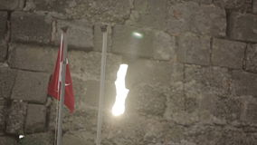 Turkish flag on a stone wall background at sunset stock footage