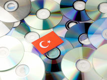 Turkish flag on top of CD and DVD pile isolated on white. Turkish flag on top of CD and DVD pile isolated Royalty Free Stock Photography