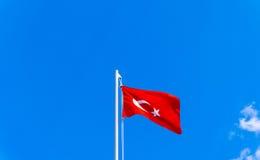 Turkish flag waving in blue sky Stock Photos