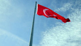 Turkish flag waving. On a cloudy blue sky background stock footage