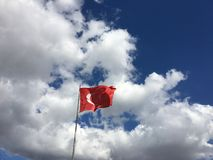 Turkish flag. Waving under the blue and cloudy sky Royalty Free Stock Photo