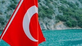 Turkish flag waving on wind on background of sea coast and mountains. National symbol of Turkey. Red Turkish flag fluttering above Mediterranean sea stock video
