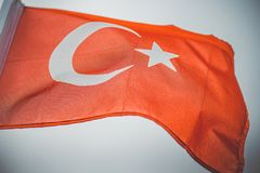 Turkish flag in the wind against the light sky stock image