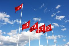 Turkish flags flutter in the wind against a blue sky. Five Turkish flags flutter in the wind against a blue sky with white clouds Stock Photos