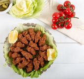 Turkish Food Cig Kofte with lemon, lettuce and parsley on silver plate.  royalty free stock photos
