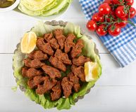 Turkish Food Cig Kofte with lemon, lettuce and parsley. On silver plate stock photography