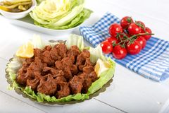 Turkish Food Cig Kofte with lemon, lettuce and parsley on silver plate.  royalty free stock photography