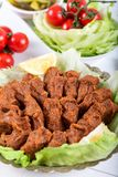 Turkish Food Cig Kofte with lemon, lettuce and parsley on silver plate.  royalty free stock images