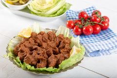 Turkish Food Cig Kofte with lemon, lettuce and parsley. On silver plate stock photo