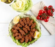 Turkish Food Cig Kofte with lemon, lettuce and parsley. On silver plate royalty free stock photography