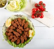 Turkish Food Cig Kofte with lemon, lettuce and parsley. On silver plate royalty free stock photo