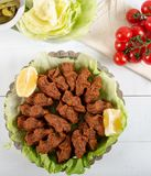 Turkish Food Cig Kofte with lemon, lettuce and parsley. On silver plate stock image