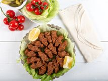 Turkish Food Cig Kofte with lemon, lettuce and parsley. On silver plate royalty free stock photos