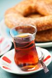 Turkish food: simit bread and cup of tea, shallow DOF. Turkish food: simit bread and cup of tea in traditional glass Stock Photos