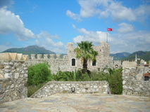 Turkish fortress. With palm in the middle. Flan on tower. Blue sky with clouds Royalty Free Stock Photography