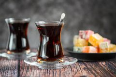 Turkish glass for tea bardak with turkish delight on dark wooden table.  stock photo