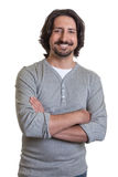 Turkish guy with crossed arms. Standing turkish guy with crossed arms, long black hair and beard laughing on an isolated white background for cut out Stock Images