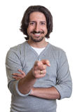 Turkish guy pointing at camera. Laughing turkish guy with long black hair and beard pointing at camera on an isolated white background for cut out Royalty Free Stock Images