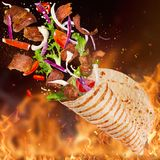 Turkish Kebab yufka with flying ingredients and flames. Freeze motion Royalty Free Stock Images