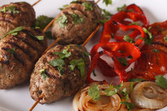 Turkish kofte kebab with grilled vegetables close-up. horizontal. Turkish kofte kebab with grilled vegetables on a plate close-up. horizontal Royalty Free Stock Photography