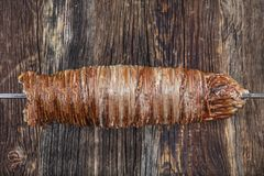 Turkish Kokorec made with sheep bowel cooked in wood fired oven. Kokorech. Kokorec made from lamb guts isolated on wooden background. Traditional Turkish stock photo