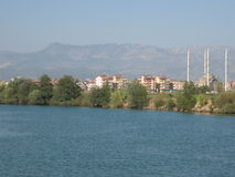 Turkish landscape: mosque, river and mountains. Landscape with mosque and modern buildings on the bank of the river, mountains behind. Recorded in Turkey Stock Image