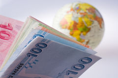Turkish Lira banknotes by the side of a model globe Stock Image
