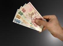 Turkish lira in hand. Turkish lira in male hand on black gradient background Stock Image