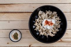 Turkish manti in a black plate with sauce on a wooden background. View from above. stock photography