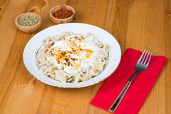 Turkish Manti (ravioli) on plate with red pepper, butter, sauce, yogurt and mint. On a wooden table Royalty Free Stock Photos