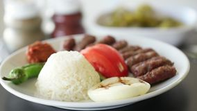 Turkish meatball inegol kofte with rice, onion, tomatoes and green pepper. Rotating shot. Turkish meatball inegol kofte with rice, onion, tomatoes and green stock video