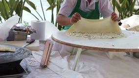 Turkish pancake gozleme. Woman making traditional Turkish pancakes (gozleme) with potatoes and cheese stock footage